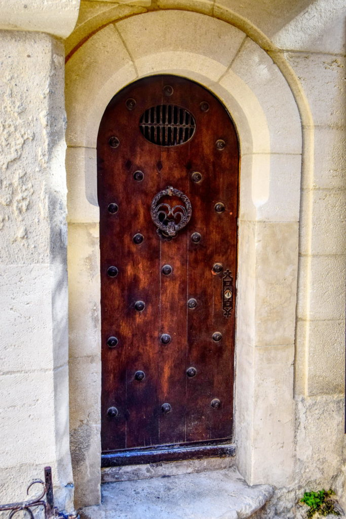 Photo of an old wooden door with beautiful ironwork, surrounded by a thick limestone wall in a typical Provencal village in the south of France.
